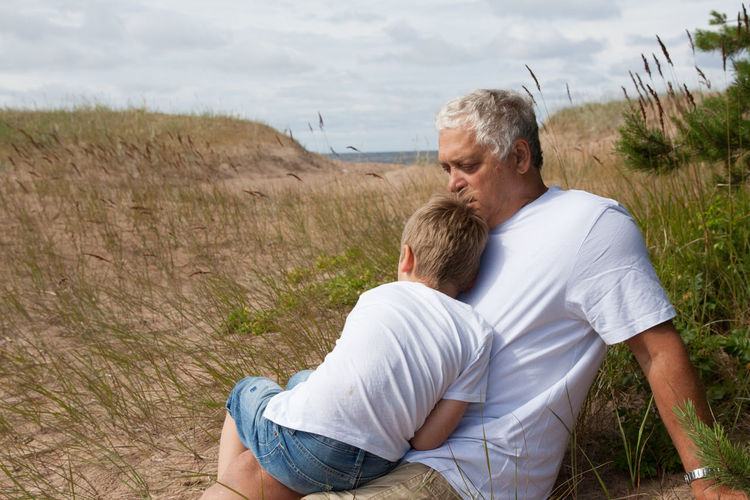 Grandfather With Grandson Resting On Field