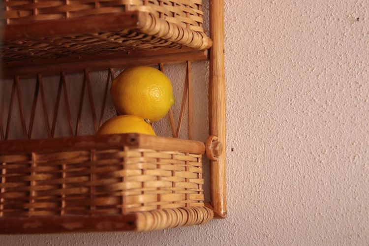 Close-up of fruits in basket against wall