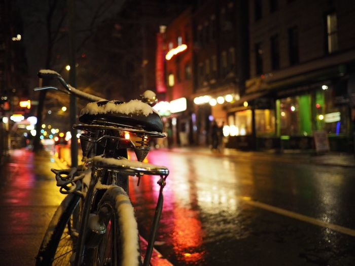 Close-Up Of Snow On Bicycle By Street At Night
