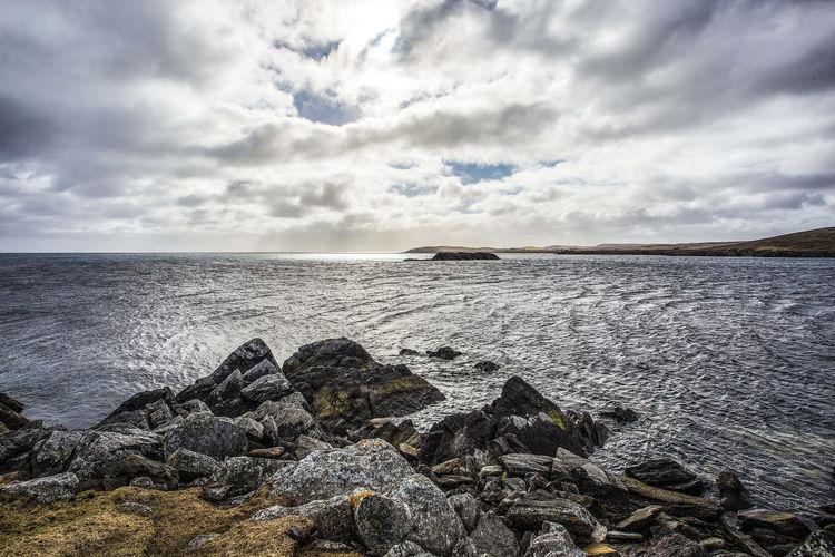 Photo taken in the UK, Scotland, Shetland, Yell Uk Scotland Shetland Sky Water Beauty In Nature Tranquility Sea North Sea Coatline Craggy Yell Horizon Over Water Cloud - Sky Rocky Coastline