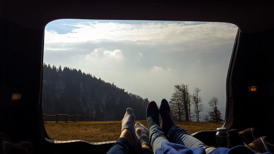 Low Section Of Couple Relaxing In Motor Home On Field