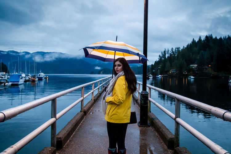 Woman standing on pier at lake