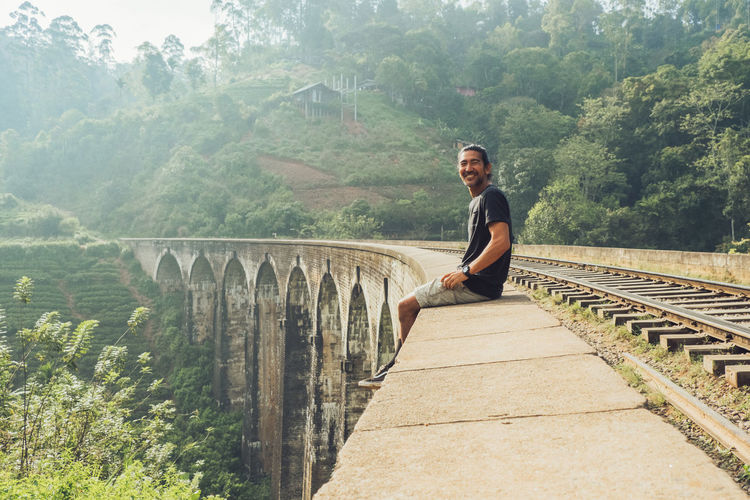 Full length of young man on bridge against trees