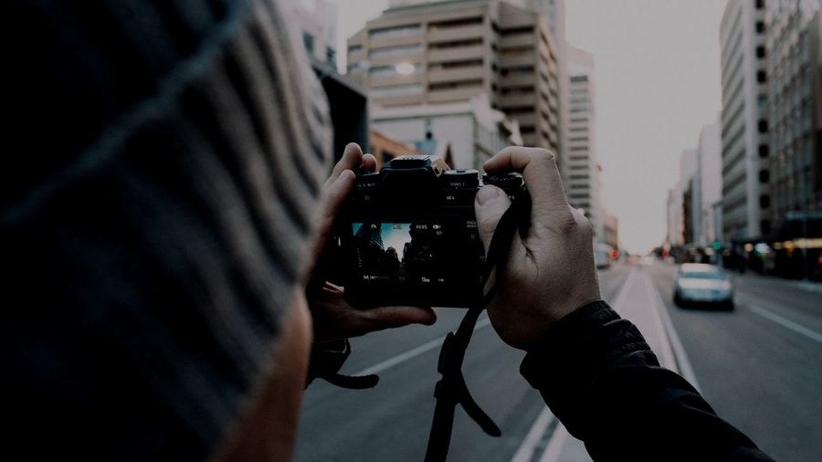 Close-up of man photographing on city street