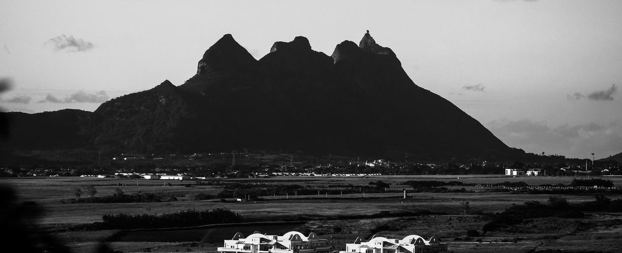 Mountain range in B&W Animal Themes Architecture Beauty In Nature Black And White Building Exterior Day Large Group Of People Mountain Mountain Range Nature Outdoors People Real People Rock - Object Scenics Sky Water