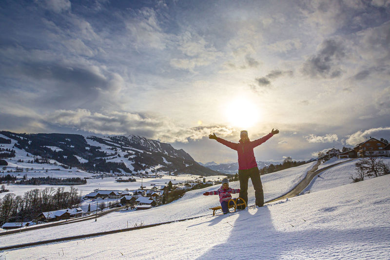 Man with arms outstretched on snowcapped mountain against sky