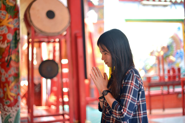 Asian woman prays respect to Chinese buddha in Chinese temple Chinese Buddha Casual Clothing Chinese New Year Day Indoors  Leisure Activity Lifestyles One Person One Young Woman Only People Praying Real People Standing Waist Up Young Adult Young Women