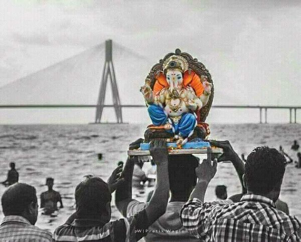 Ganpati back to home Suspension Bridge Water Connection Sitting Bridge - Man Made Structure Travel Destinations Tourist Holding Day Vacations Tourism Outdoors Focus On Foreground Sea International Landmark Multi Colored Cloud - Sky