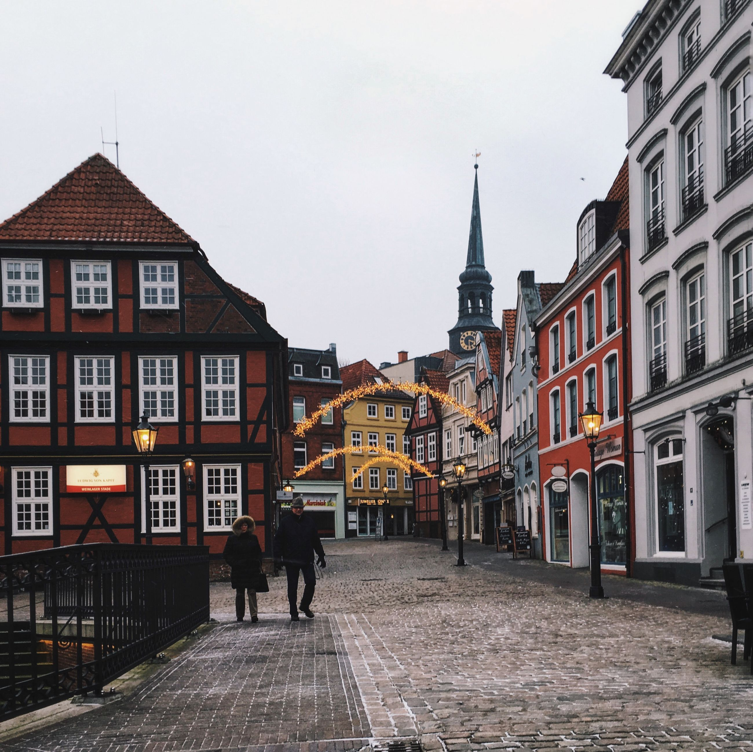 building exterior, architecture, built structure, city, the way forward, street, walking, sky, clear sky, church, cobblestone, incidental people, residential structure, facade, old town, men, residential building, city life, religion