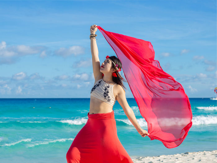 Woman with red umbrella standing on beach