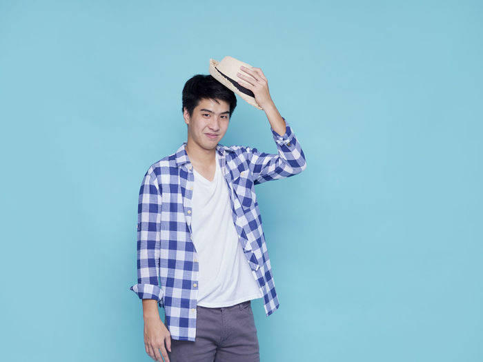 Young man standing against blue background