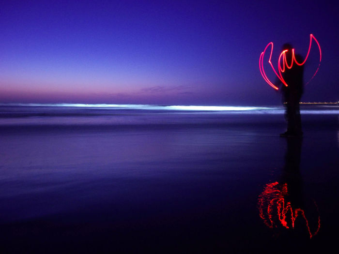 Light painting at beach against sky