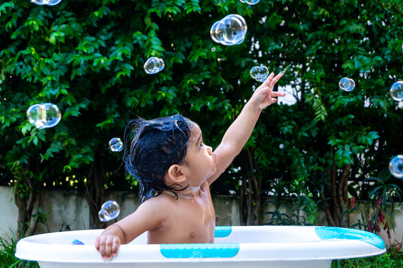 Full length of shirtless boy with bubbles in water
