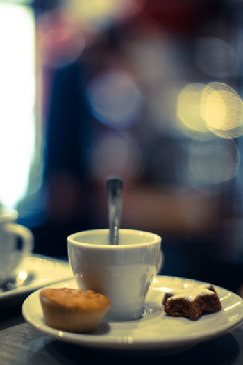 Close-Up Of Coffee Cup With Cupcakes And Cookie On Table