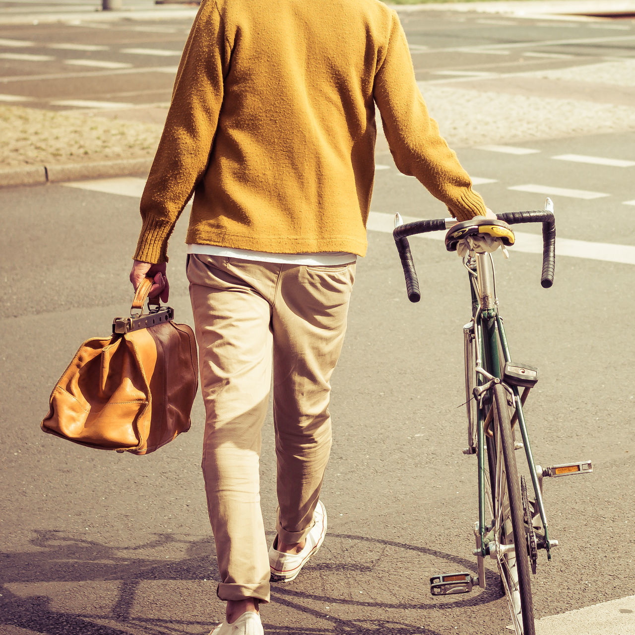 Low section rear view of man carrying bag while walking with bicycle in city