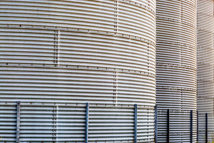 A full frame photograph of large grain elevators on a farm