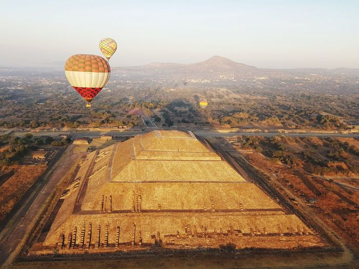 View of hot air balloon flying over landscape and ancient pyramid