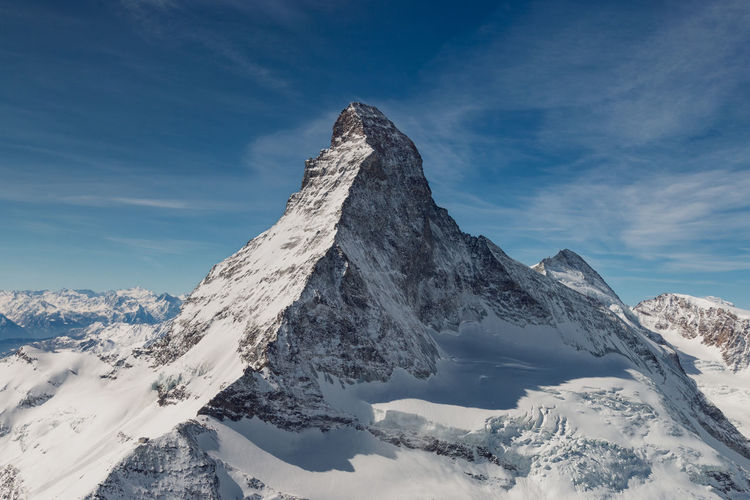 Aerial view of majestic and world famous Matterhorn mountain in front of a blue sky, Switzerland Snow Mountain Cold Temperature Winter Scenics - Nature Beauty In Nature Sky Tranquil Scene Tranquility Mountain Range Snowcapped Mountain Cloud - Sky Mountain Peak Nature Non-urban Scene Environment Idyllic Day Landscape No People Formation Majestic Matterhorn  Aerial Landmark