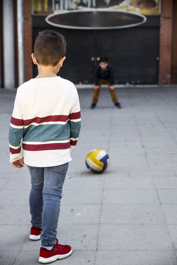 Friends playing with soccer ball on footpath
