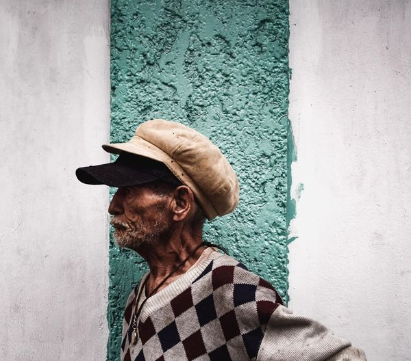 Side View Of Senior Man Standing Against Wall