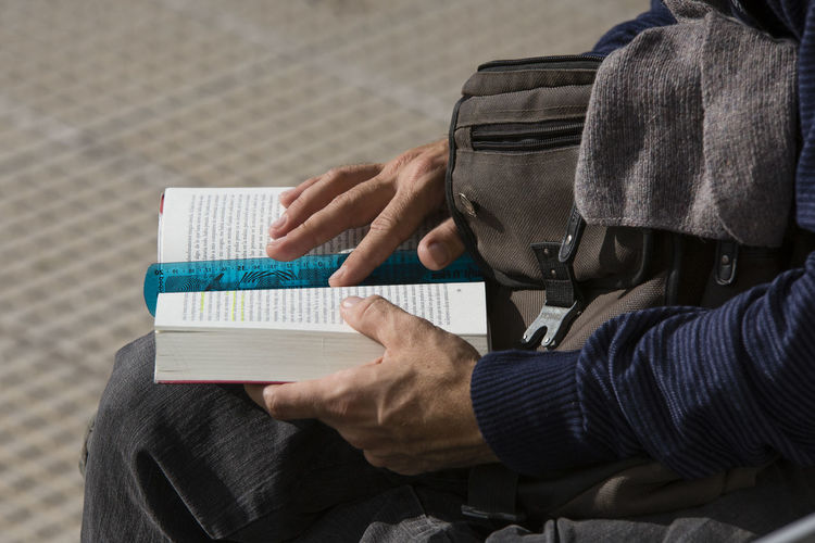 Midsection of man reading book while sitting outdoors