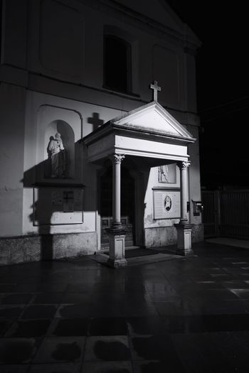 Statue against building at night