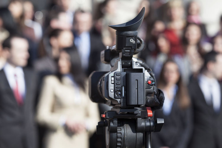 Close-up of camera against people