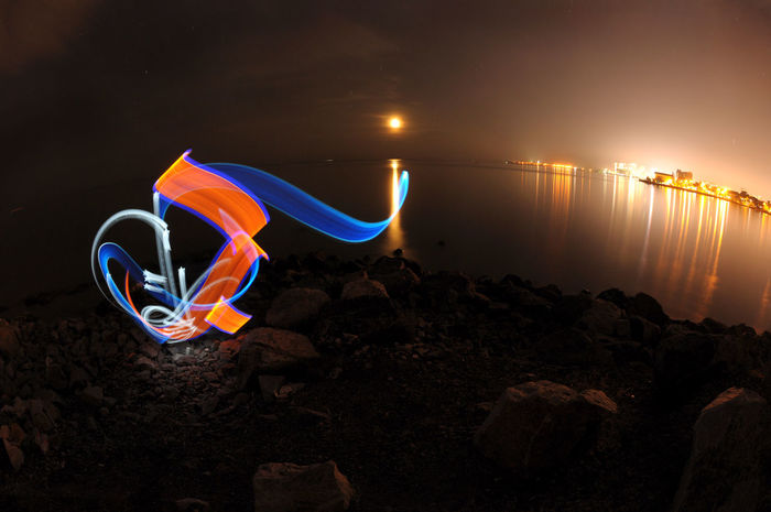 Abstract light graffiti or light painting with moon and city with reflection (using led lights and slow shutter photography) Adventure Arabic Calligraphy Bulgaria Calligraffiti Calligraphy City City Lights Fisherman Illuminated Landscape LED Light Led Lights  Light Graffiti Light Painting Motion Motion Light Night Outdoors Reflection Rock Sea Slow Shutter