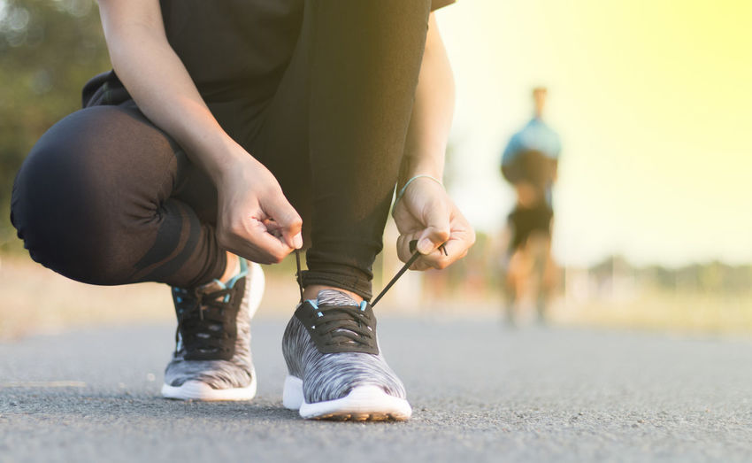 woman tying shoe of female sport fitness runner getting ready for jogging outdoors. Tying Body Part Close-up Day Exercising Healthy Lifestyle Human Body Part Human Foot Human Leg Leisure Activity Lifestyles Low Section One Person Outdoors Real People Shoe Sport Sports Clothing Vitality Women