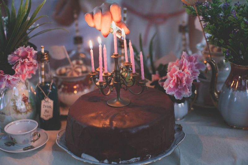 Cropped hand lighting candles on chocolate cake