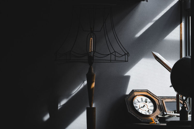retro lamp, clock and stuff in living room against sun light and shadow from window Lamp Shadow Clock Sun Light Decor Decoration Wall Background Wooden Home Old Antique Nobody Wood Retro Shine Façade Style Glow Outside Indoor Incandescent Power Metal Illumination Electric Backdrop Decorative Table Living Design Furniture House Interior Room Concept Vintage Desk Object Sunlight Equipment Space Architecture Decorate Window Empty Clean Minimal Time