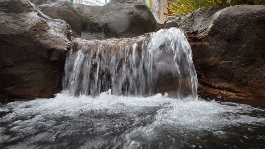 Small waterfall in the water park. Waterfall Water EyeEm Selects Water Motion Waterfall Long Exposure Beauty In Nature Flowing Water Waterfront Scenics - Nature Rock - Object Blurred Motion Splashing Nature