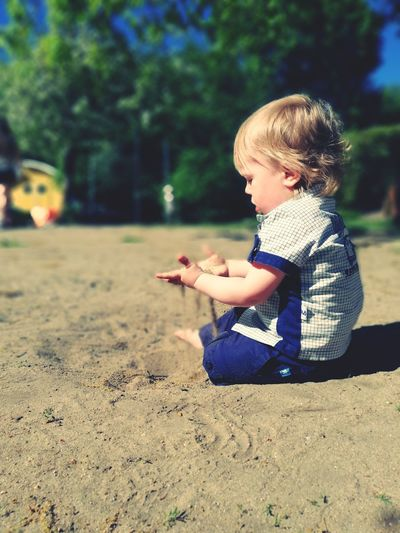 Side View Of Boy Sitting On Sand At Playground