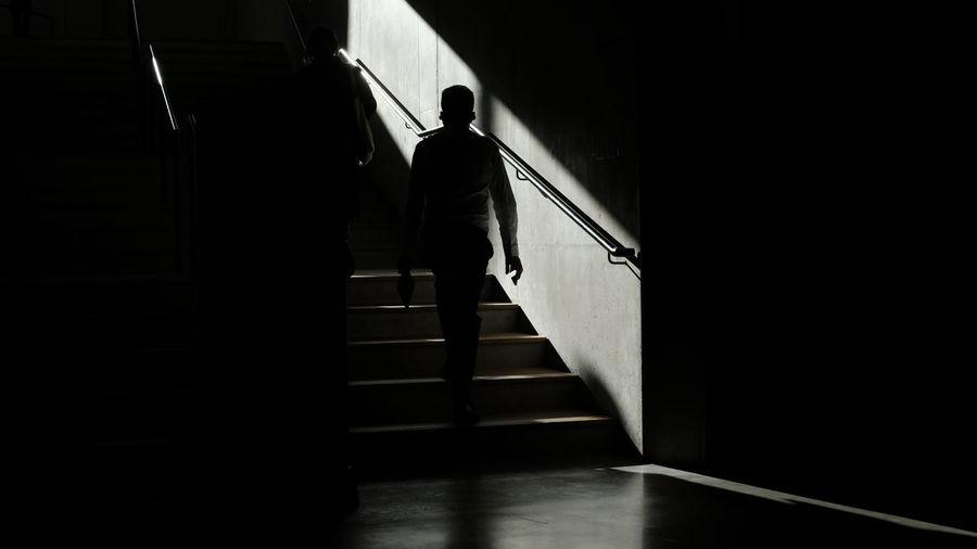 Rear view of silhouette man walking in corridor of building