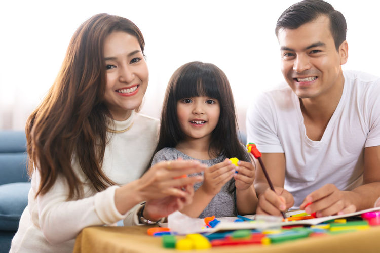 Portrait of happy family daughter girl is learning to use colorful play dough blocks toy together with parent Asian  Asian Girl Women Hapy Thai Ethnicity Japanese  Korean Taiwanese Smiling Family Love Daughter Mom Happiness Mother Dad Daddy Girl Girls Parent Lerning Drawing Development Education Creativity Color Pencil Living Room Home House Females Togetherness Childhood Emotion Leisure Activity Group Of People Child Indoors  Front View Adult Portrait Positive Emotion ASIA