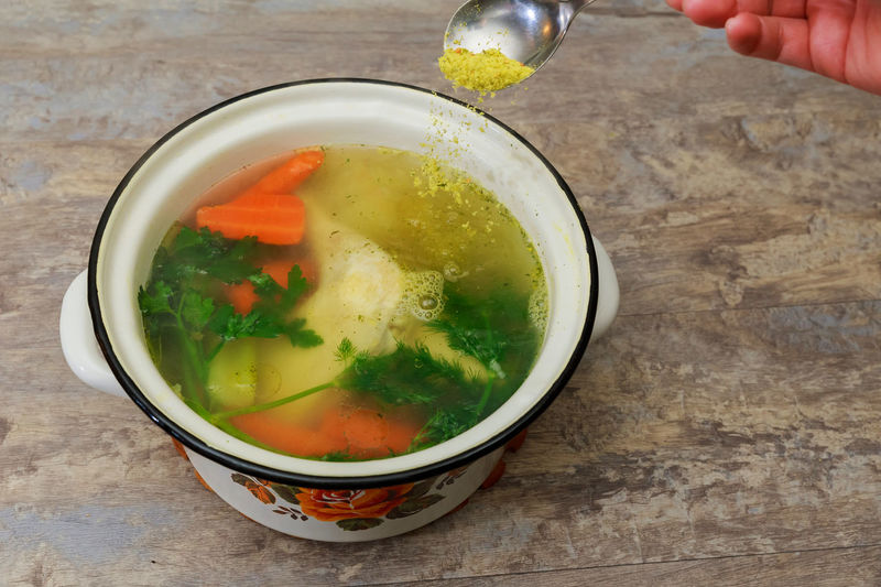 Cropped hand adding ingredient in soup bowl