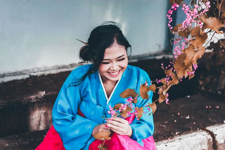 Young woman holding flower outdoors