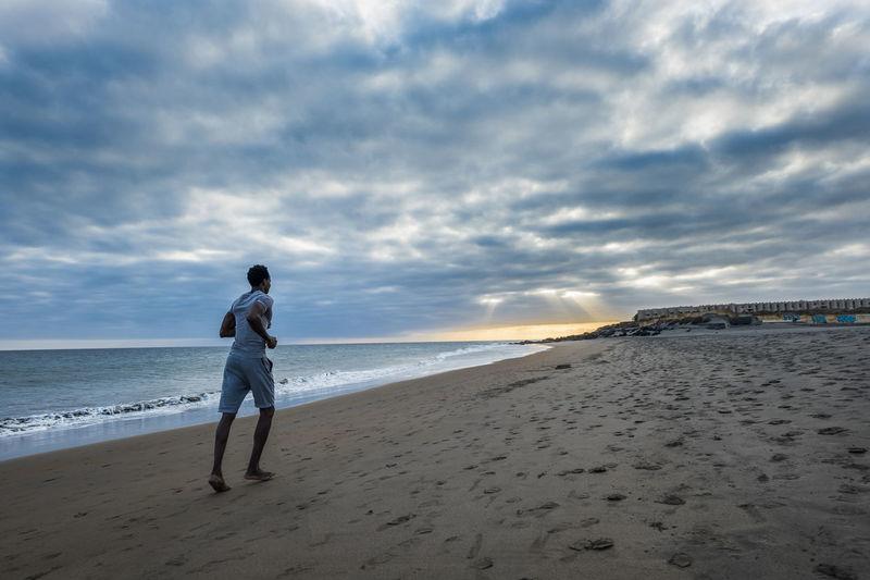 Full length of man running at beach against cloudy sky