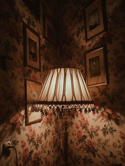 Illuminated electric lamp on bed by wall at home