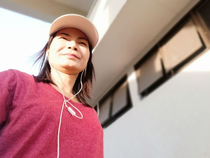 Smiling woman wearing in-ear headphones while standing against building
