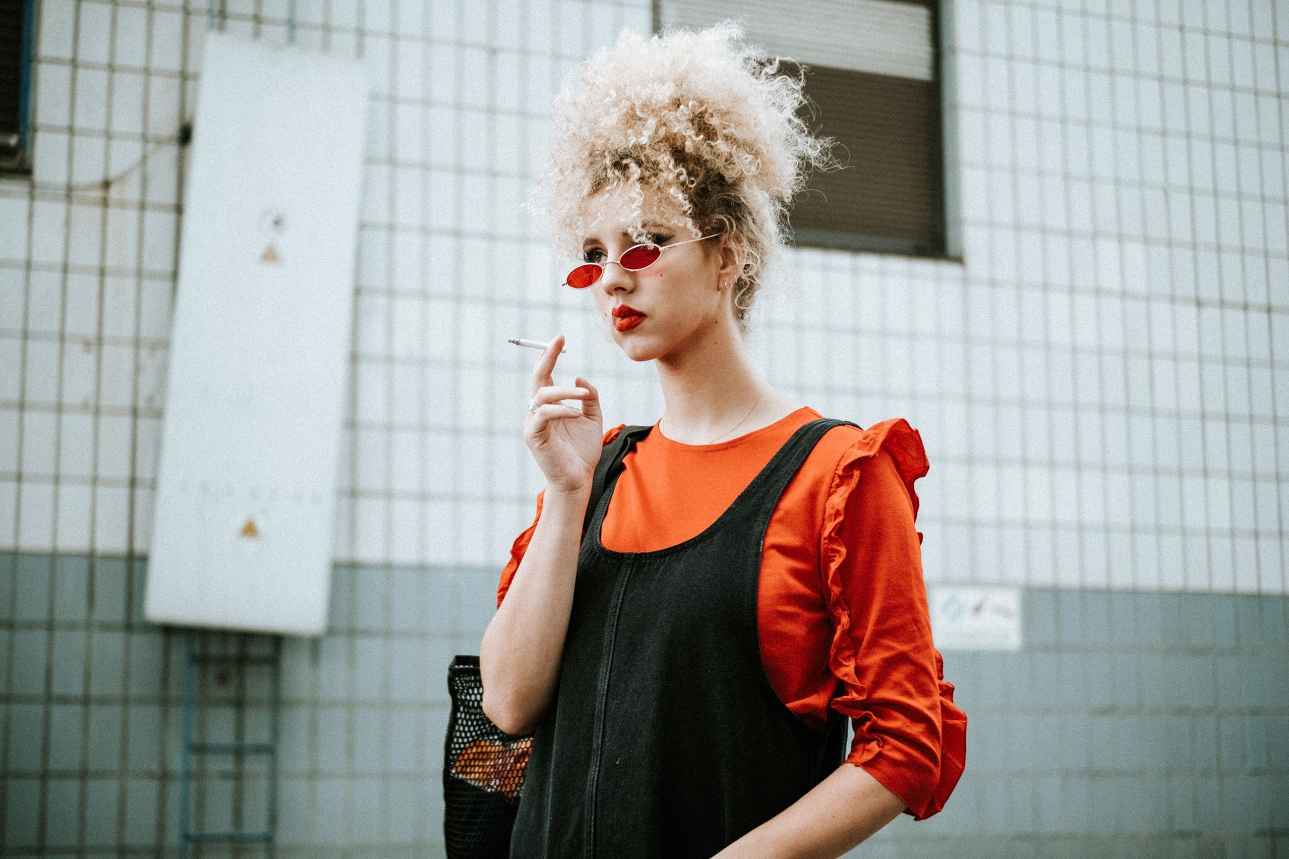 one person, cigarette, standing, curly hair, young adult, architecture, smoking issues, lifestyles, hair, hairstyle, adult, real people, portrait, women, casual clothing, bad habit, fashion, beautiful woman, outdoors