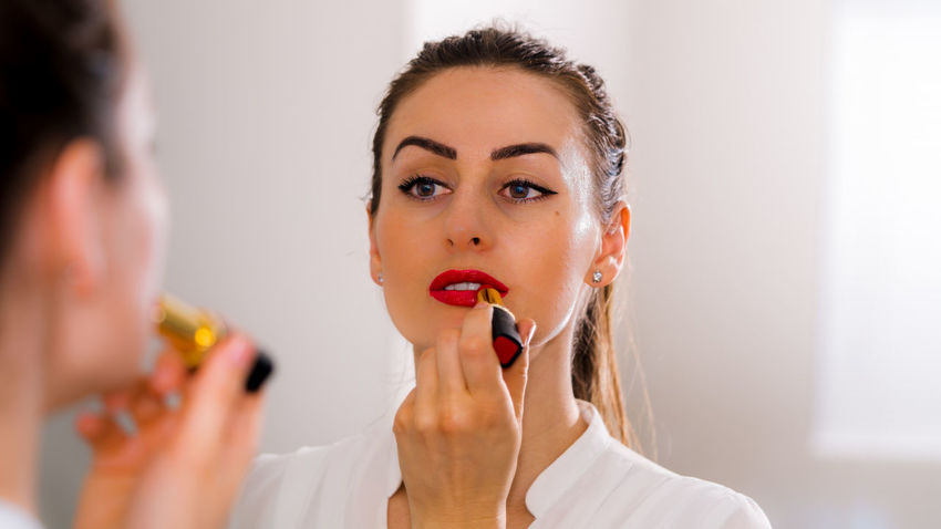 Close up of a woman putting red lipstick while looking in the mirror. Adult Applying Bathroom Beautiful Woman Beauty Beauty Product Beauty Treatment Body Care Close-up Domestic Bathroom Headshot Human Body Part Human Lips Indoors  Lifestyles Make-up Mascara Mirror Real People Red Lipstick Reflection Self Improvement Women Young Adult Young Women