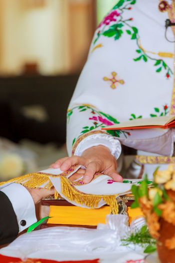 Close-up of bride with groom putting hands on religious book during wedding