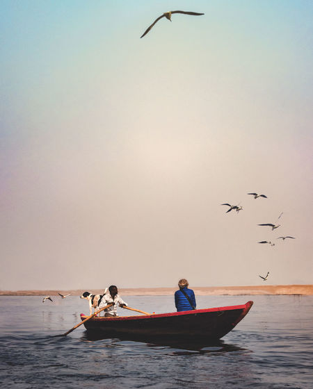 People sitting in boat over sea against flying birds