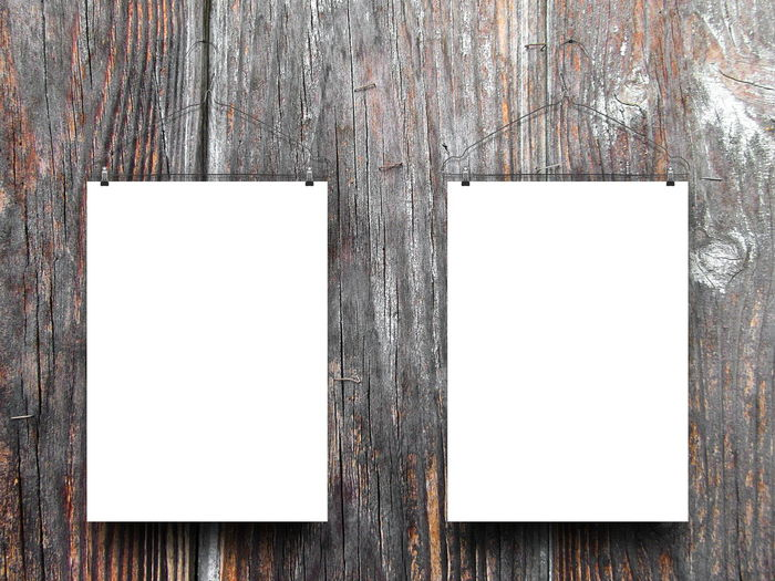 Low angle view of blank papers hanging on wooden wall