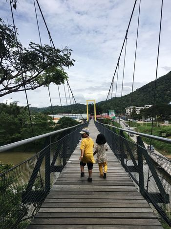 Girl Boys Kids Yellow Sky Rear View Cloud - Sky Bridge Nature Women Architecture Real People Walking Day The Way Forward Built Structure Connection Plant Direction Full Length Tree Men Bridge - Man Made Structure Child