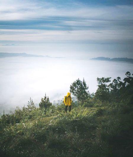 Full length of hiker walking on mountain against sky