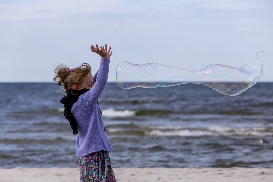 Animal Themes Beach Beauty In Nature Bubble Wand Day Focus On Foreground Horizon Over Water Leisure Activity Lifestyles Motion Nature One Person Outdoors People Real People Sand Sea Sky Standing Water Young Adult Young Women
