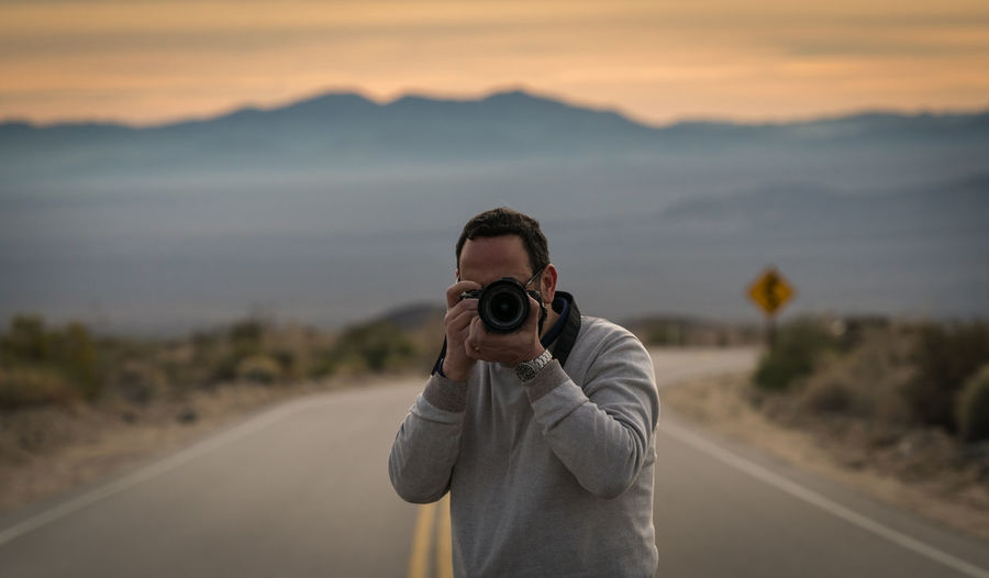 Man photographing on road