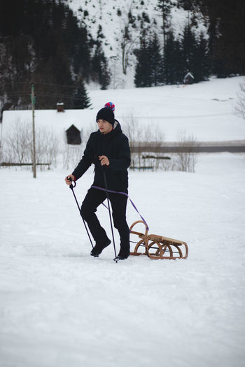 Hiker pulls to the top of a wooden sled for a ride on the piste. portrait of a man pulling a sledge.